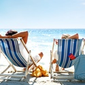 Big_rear_view_of_a_couple_on_a_deck_chair_relaxing_on_the_beach