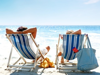 Overview_rear_view_of_a_couple_on_a_deck_chair_relaxing_on_the_beach